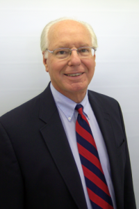 A photograph of Dan Kaercher in a suit and tie
